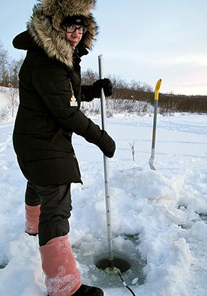 Maria Kämäri pitää virtausnopeusmittaria 60 sekuntia paikoillaan jään alareunassa.